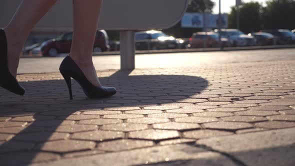 Thumbnail for Female Legs in High Heels Shoes Walking in the Urban Street Near Auto Parking. Business Woman