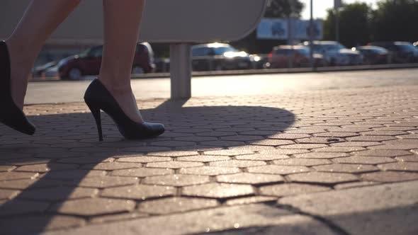 Female Legs in High Heels Shoes Walking in the Urban Street Near Auto Parking. Business Woman