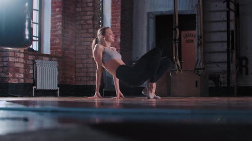 A Young Skinny Woman Doing Gymnastics Exercises in the Gym