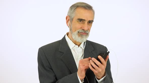 Thumbnail for An Elderly Man Listens To Music on a Smartphone with a Smile - White Screen Studio