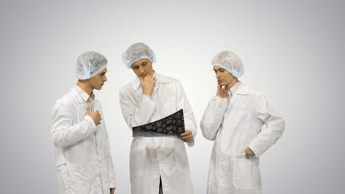 Three Doctors Rhythmically Look at An X-Ray Photo of A