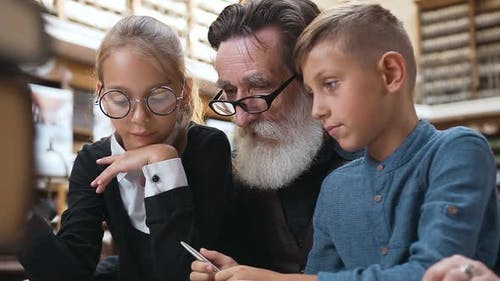 Grandchildren Sitting at the Library Table with Their Respected Eldery Grandpa