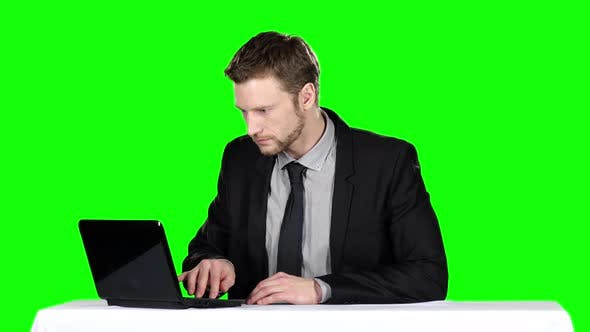 Cover Image for Businessman Sitting at the Table and Uses Notebook, Green Screen