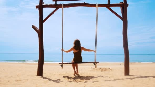 Cover Image for A Young Woman in Green Swimming Suit Swinging on a Swings on the Clean Beach