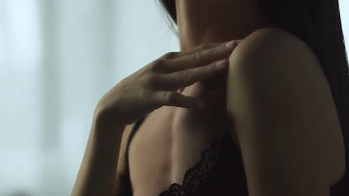 Young brunette woman in lingerie gently touching soft skin, body care products