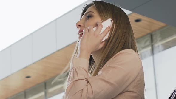 Thumbnail for Cute female office worker standing outdoors during break, talking on phone