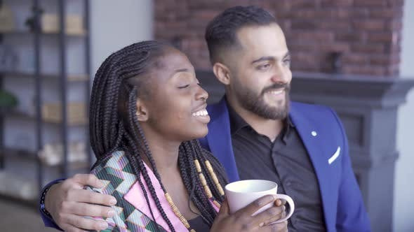 Cover Image for African American Woman and Caucasian Man Looking at the Window and Smiling. Happy Couple with a Cup