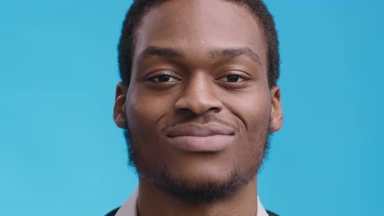 Close Up Portrait of Cheerful African American Guy Smiling To Camera, Blue Studio Background