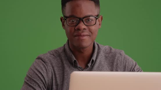 Thumbnail for Millennial man sitting at desk with computer smiling on green screen