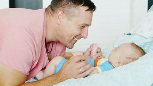 Happy Fatherhood. Young Attractive Man Smiles at His Young Son