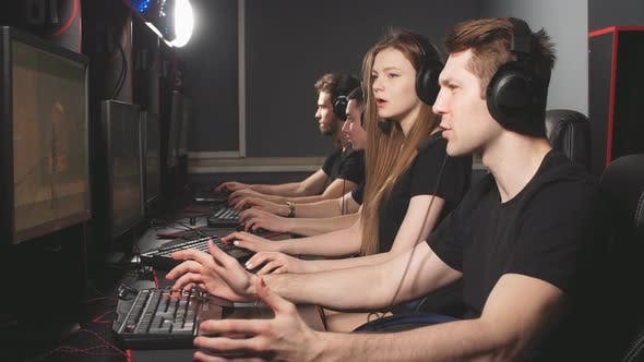 Thumbnail for Group of Adult Male and Female Gamers Sitting in a Row Behind the Monitors, Play in PC Gaming Centre