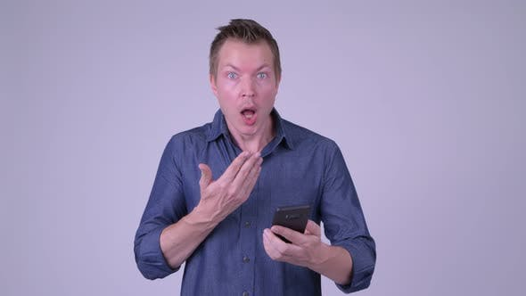 Thumbnail for Portrait of Young Businessman Using Phone and Looking Shocked