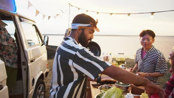 Man Preparing Street Food for Young Multiethnic People on Summer Festival