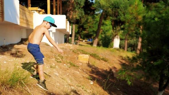 Ребенок осторожно пробивает путь вниз на наклонном грунте