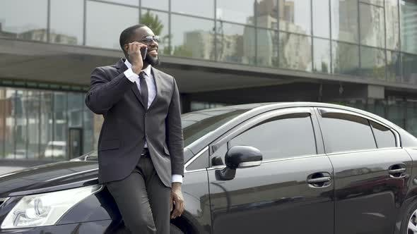 Thumbnail for Afro-American Man Talking on Phone With Smile on Face Near Office