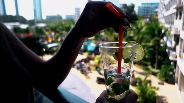 Thumbnail for Woman Holds Straw in Half Empty Glass with Mojito Cocktail