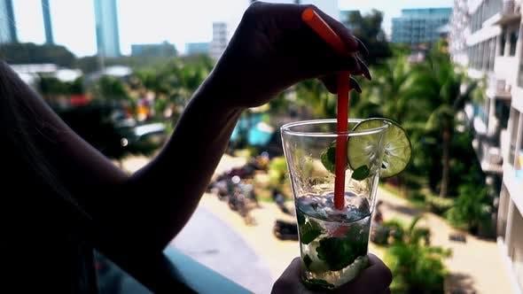 Thumbnail for Frau hält Stroh in halb-leerem Glas mit Mojito Cocktail