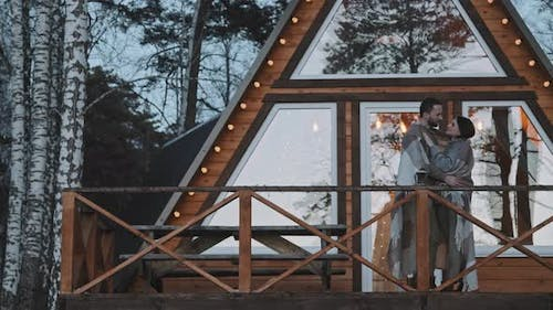Couple Hugging on Porch of A-Frame Cabin