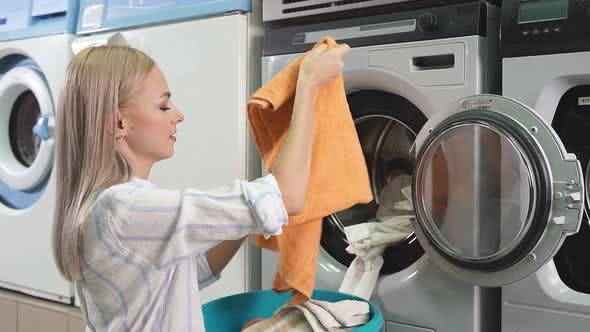 Young Blonde Puts Laundry in the Washing Machine in the Public Laundry Room