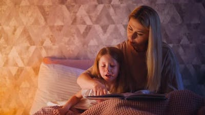 Mommy Teaches Girl to Read Following Line with Finger on Bed