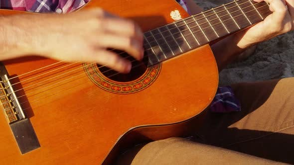 Thumbnail for Close up of young person playing acoustic guitar