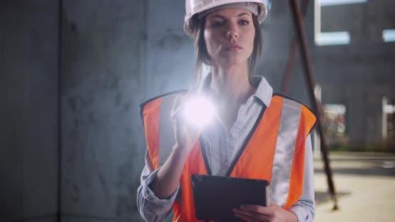 Thumbnail for Ingenieurin arbeitet und leuchtende Taschenlampe an der Kamera auf der Baustelle