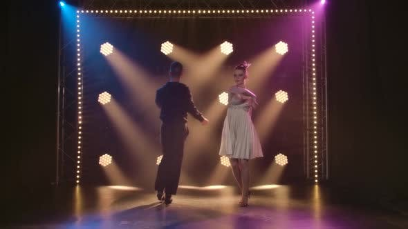 Ballroom Dancers Are Dancing on a Black Background with Studio Stage Lighting. Slow Motion.