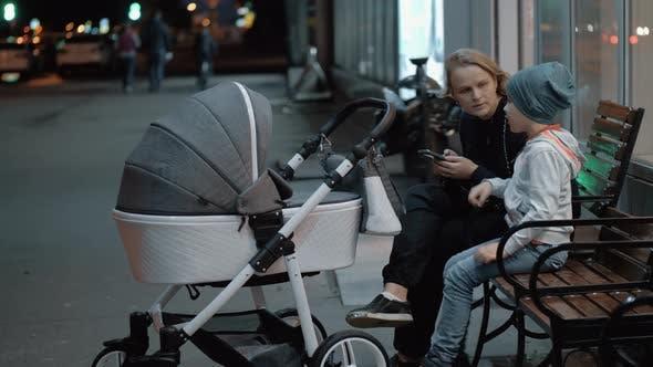 Frau mit Baby und älterem Sohn verbringen Abend draußen
