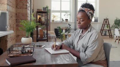 Black Woman Writing in Notebook