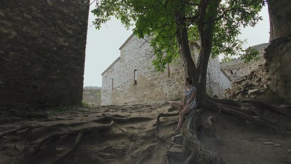 Thumbnail for Girl Resting Sitting on Roots of Tree in Territory of Ancient Defensive Fortress with Stone Masonry