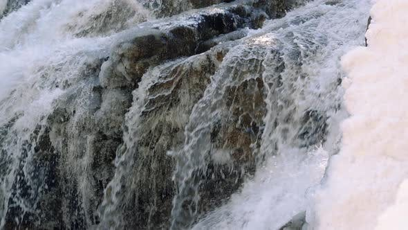 Thumbnail for Slow Motion Snowy Waterfall Following White Water Over Rocks And Ice