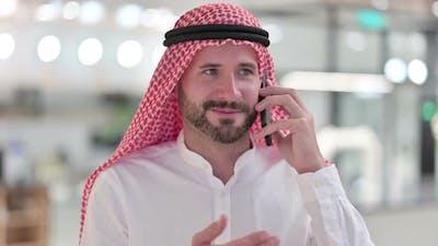 Cheerful Arab Businessman Talking on Smartphone