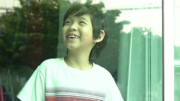 Asiatisches Kind, das lächelt und aus dem Fenster