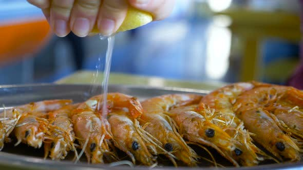 Red Shrimps on Plate and Hand Squeezing Fresh Lemon Juice
