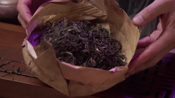 Thumbnail for Männer Hände über einen Holztisch Halten Sie eine natürliche Tasche und Blatttee und schütteln Sie den Tee. Zeitlupe.