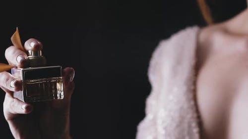 Lady in Shiny Dress Sprays Fragrance on Black Background