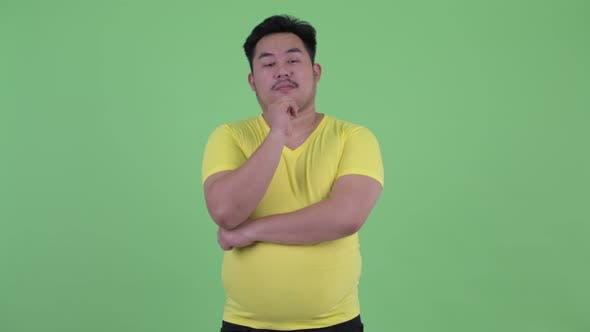 Thumbnail for Happy Young Overweight Asian Man Thinking and Looking Up