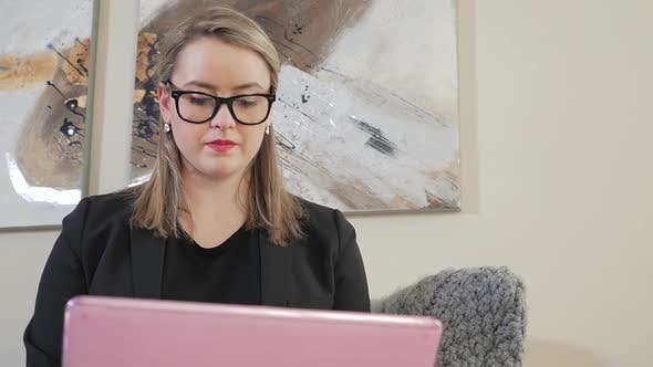 Thumbnail for A Young Female Business Entrepreneur Looking Down And Typing On Her Laptop