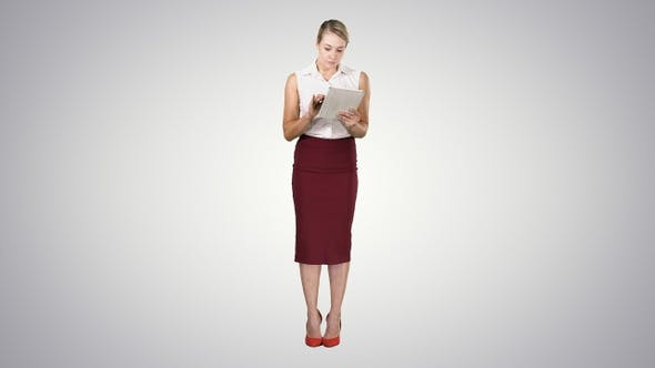 Thumbnail for Attractive businesswoman using a digital tablet while standing
