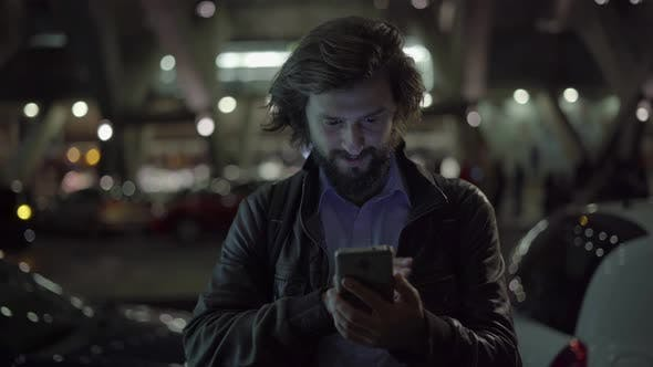 Thumbnail for Smiling Caucasian Man Using Gadget at Night in Urban City