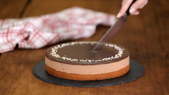 Thumbnail for Confectioner hands cut by knife chocolate mousse cake.