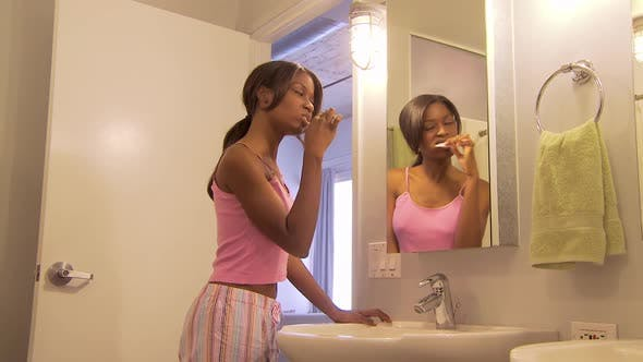Thumbnail for Young woman brushing teeth