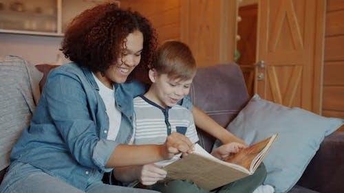 Joyful Afro-American Girl Babysitter Reading Funny Story To Happy Child Indoors