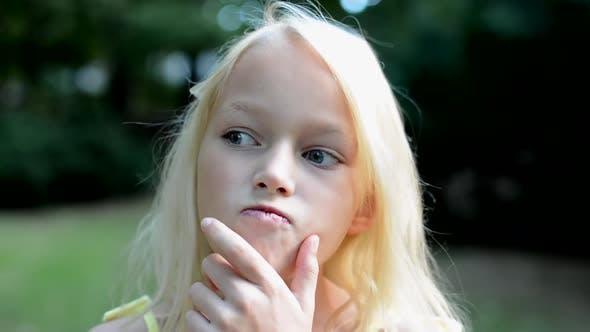 Thumbnail for Little Smart Girl Think in the Park mit Hand unter dem Kinn - Detailansicht