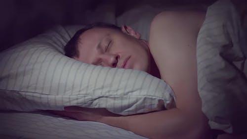 Junger Mann geht nachts ins Bett und schläft sofort ein