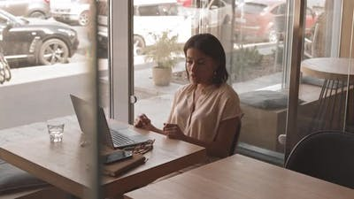 Young Woman Videocalling in Cafe