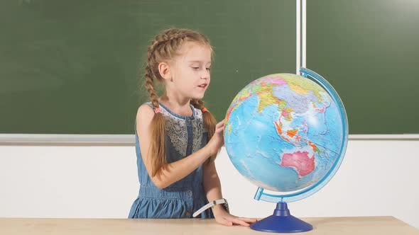 Thumbnail for School Girl with Globe in Classroom Chalkboard on Background