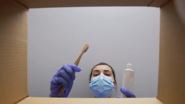 Woman in Mask Packing Box with Dental Products