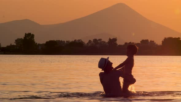 Cover Image for Father and Son Having Fun in the Water, Sea on Dusk on Background. Happy Father Spends Time with