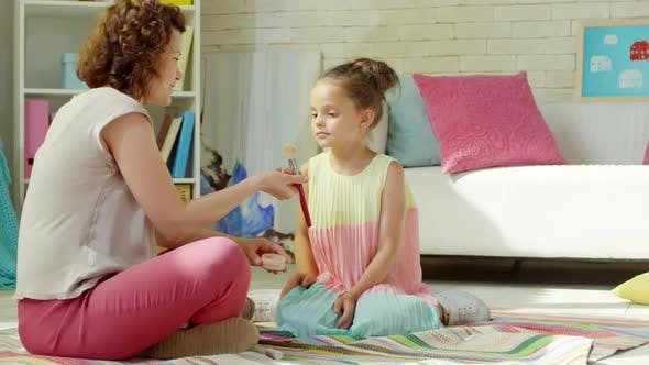Thumbnail for Mom Teaching Little Daughter How to Use Face Powder